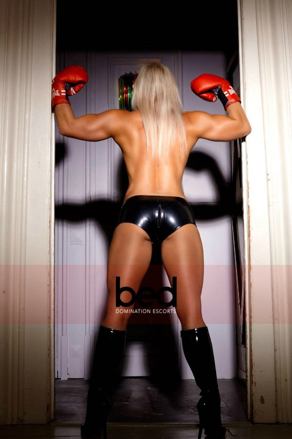 Mistress Cassandra topless wearing boxing gloves and boots
