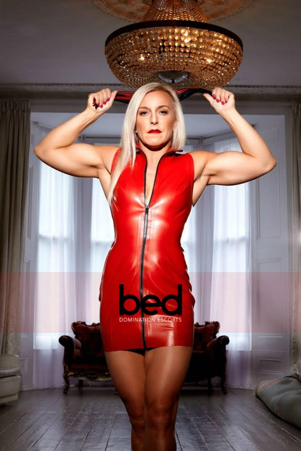 Mistress Cassandra in red dress flexing her muscles