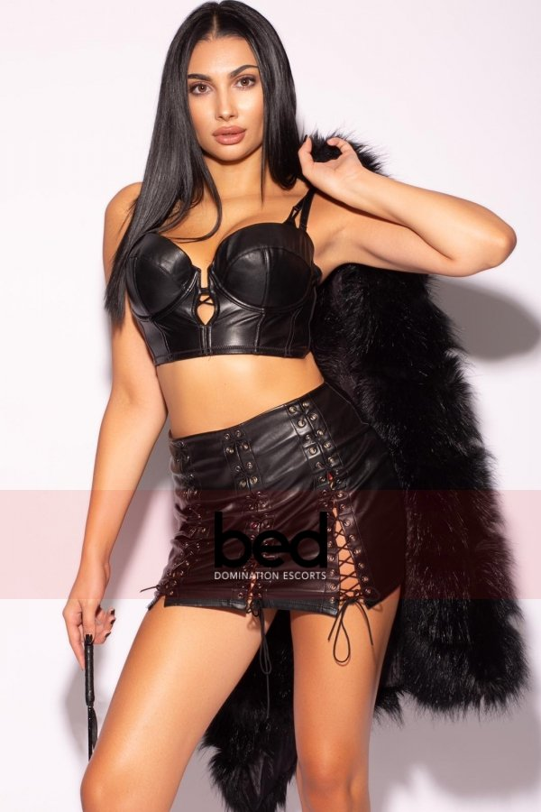 Mistress Leona holding a fur coat and whip wearing a black bra and panties