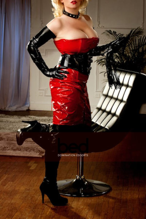 Mistress Charlotte kneeling on a chair wearing a red latex dress