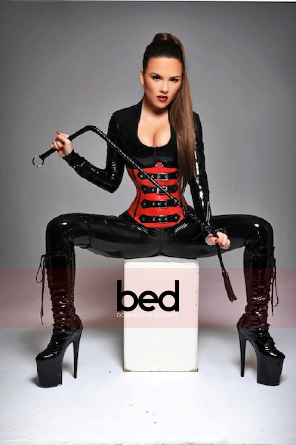 Mistress Jessica with her legs spread as she sits on a box wearing a black full body suit