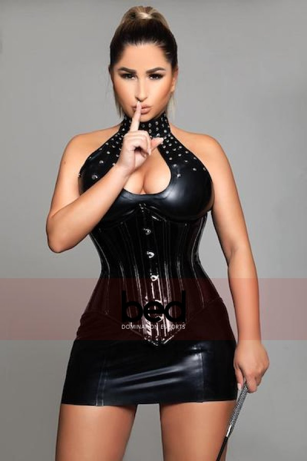 Mistress Kate wearing a black latex suit shhh